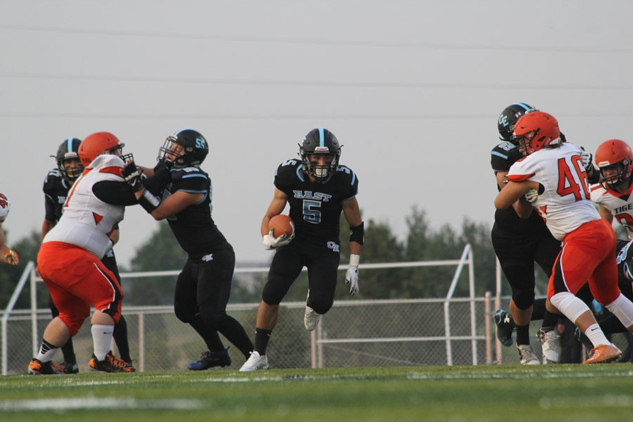 Senior running back Uriah Gracia, runs right up the middle on the Tigers line to contribute to the victory against the Rock Springs Tigers on August 28.
