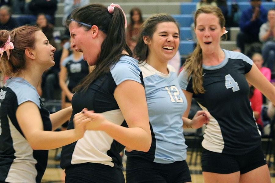 The Lady T-bird varsity volleyball team celebrates after the ball hits the ground on the opponent's side.