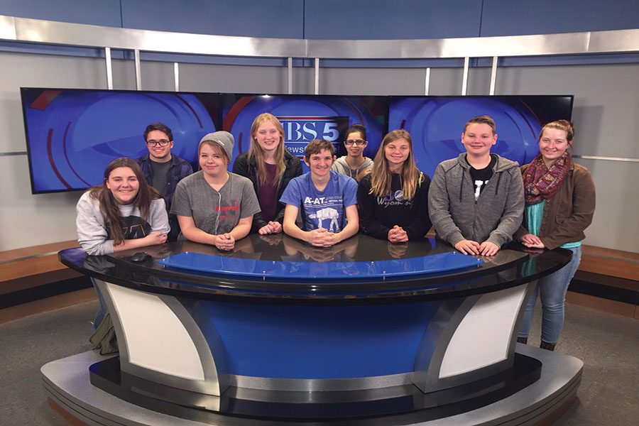 The Thunderbolt staff takes their opportunity to take a group photo in front of the anchor's desk at CBS News Channel 5.