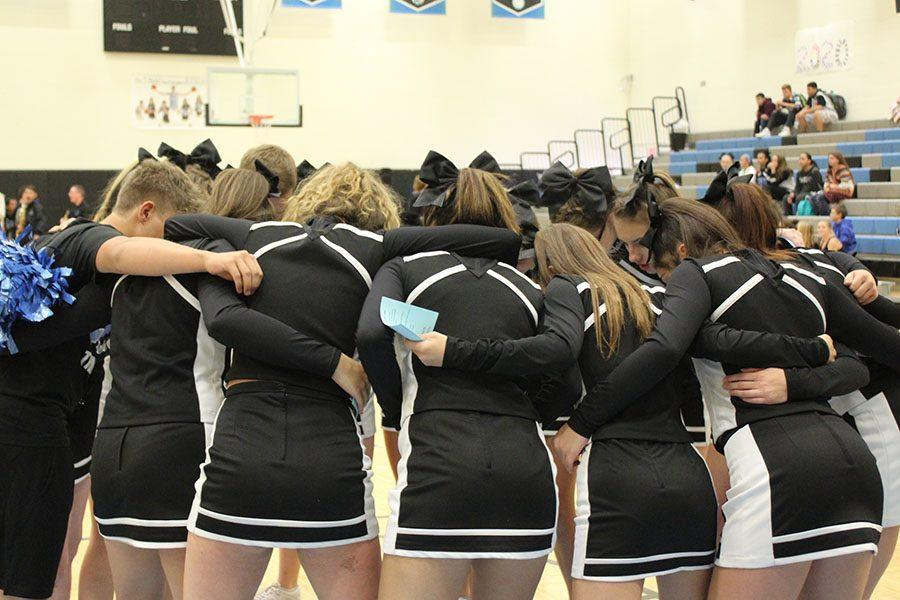 Varsity Cheer Squad joins in a huddled to get excited for the Pep Rally.