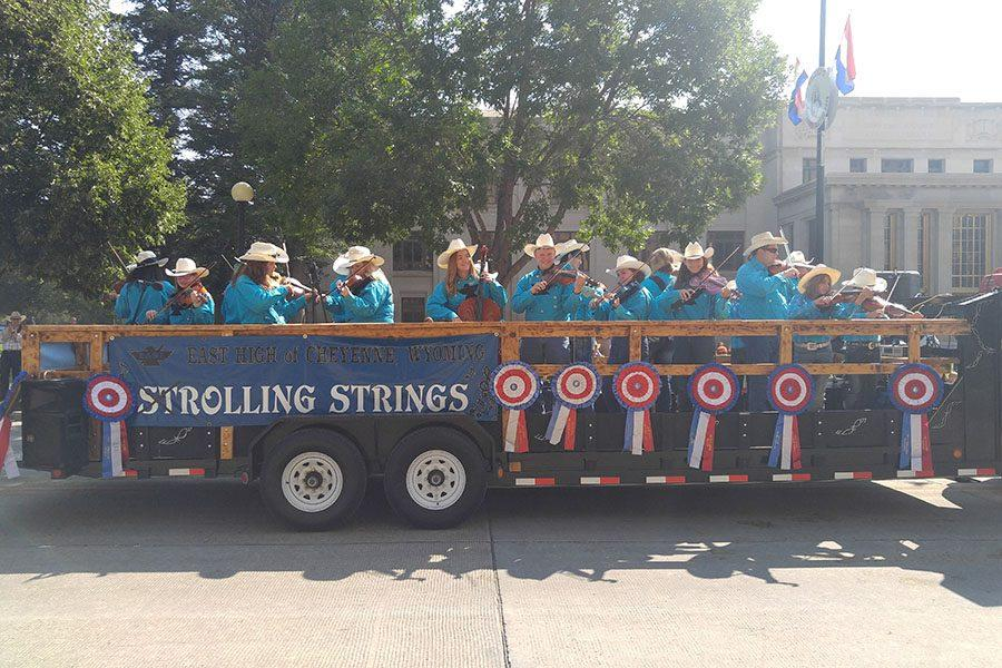 Strolling Strings rolls down the Cheyenne Frontier Days parade route, smiling at the crowd as they go.