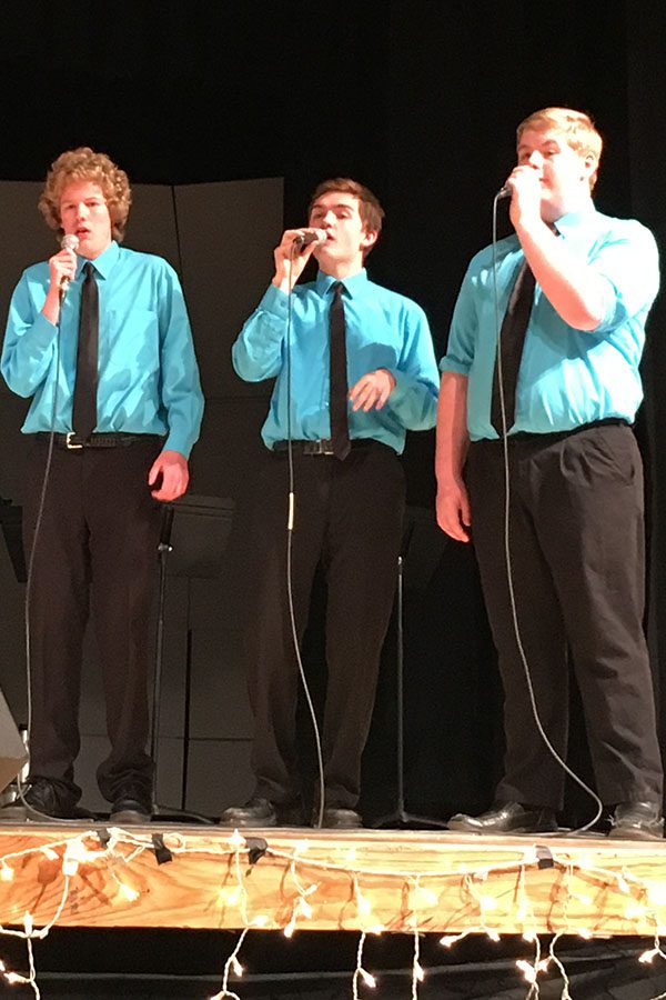 Zamboni Brown, Liam Guille, and Jonathan Greathouse sing at a benefit concert. All three students are part of the East High Singers.