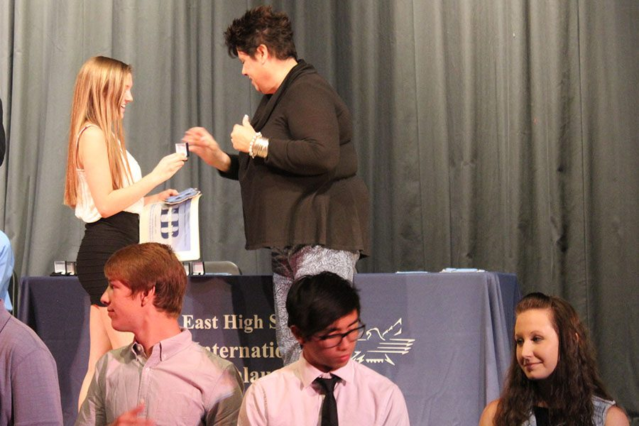 Junior Abby Shameklis receives her IB pin and letter from Mrs. Zumo at the end of the IB Induction Ceremony.