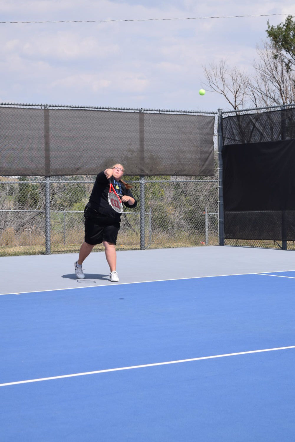 Senior Delaney Schmidt swings at a tennis tournament in early September in preparation for the State Competition.