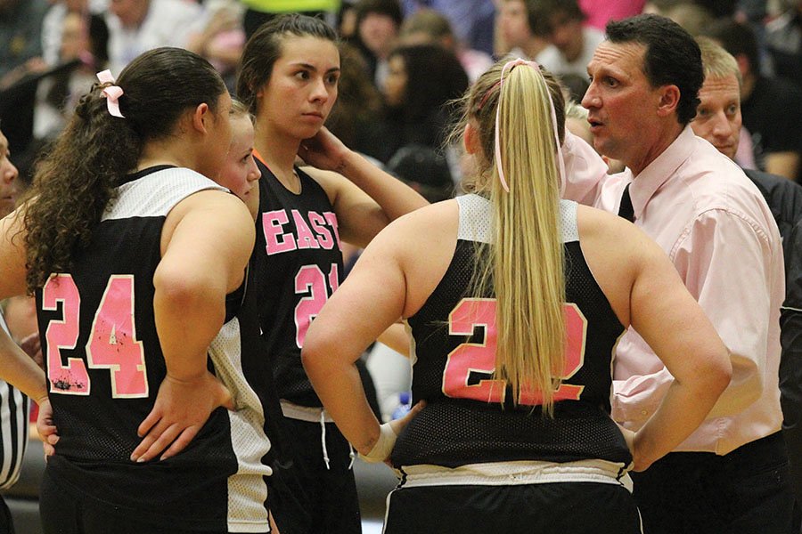 East High Varsity girls basketball players meet with Coach Horsley at the Pink Game.