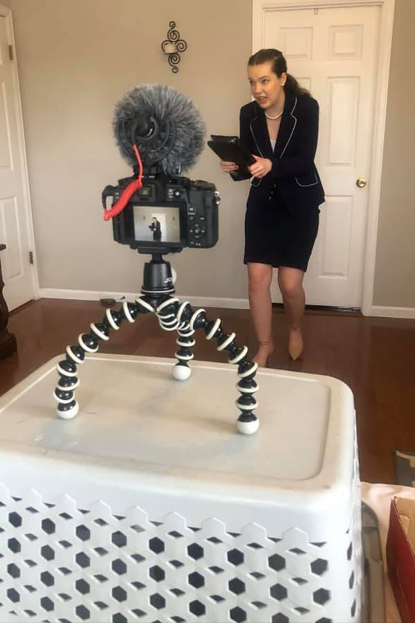 Danielle Schulz films her presentation with a camera and laundry basket tripod.