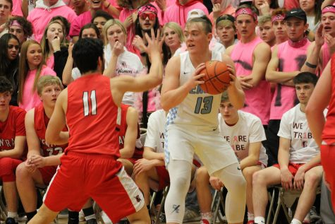 Surrounded by a sea of red, junior Graedyn Buell looks to pass inside during the Pink Game from earlier in the season. The Thunderbirds knocked the highly touted Indians out of the regional tournament, denying them a shot at a state title.